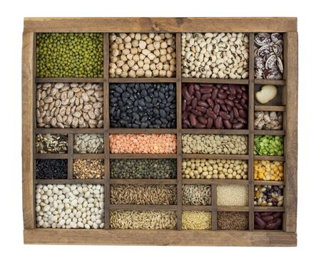 typesetter: vintage, wooden typesetter case with variety of beans, lentils, peas, grains and seeds isolated with path Stock Photo