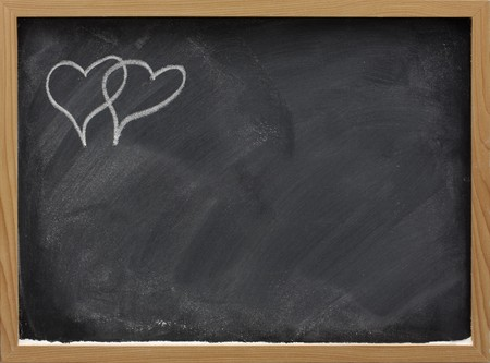 smudge: blackboard in wooden frame with eraser smudges and two interlaced hearts sketched with white chalk in a corner, copy space