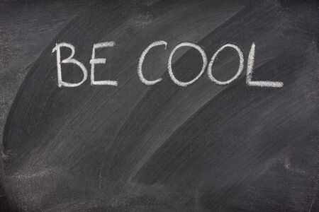 Be Cool phrase handwritten with white chalk on a blackboard with eraser smudges