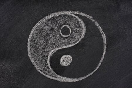 oneness: yin e yang simbolo tracciato con il gesso bianco su una lavagna con gomma sbavature