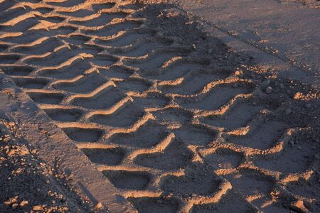 big tire tracks in sand at construction site, sunset light Stock Photo