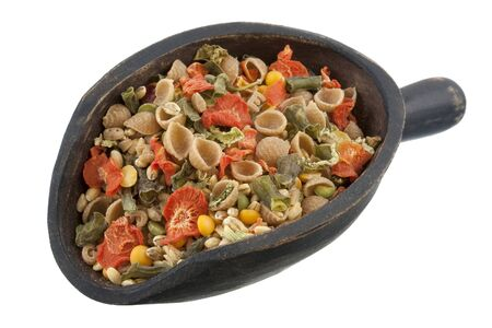 a rustic, wooden scoop of vegetable soup mix including whole wheat pasta, carrots, peas, leeks, green beans, bell peppers, corn, celery and onions, isolated on white Stock Photo - 4225526