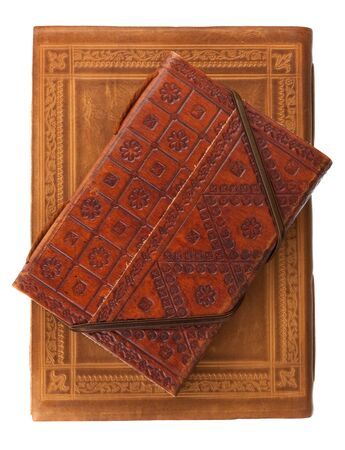 two diary books in red brown and red leather covers with rich stamped ornament isolated on white