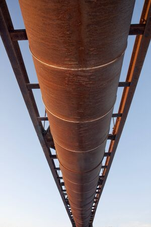 suspended rusty pipe (irrigation ditch aqueduct) shot from below against sky Stock Photo - 4225545