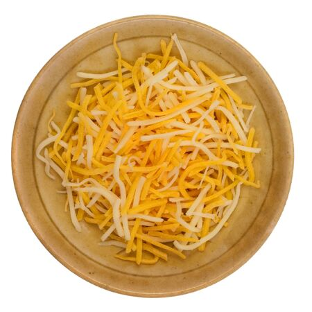 monterey: shredded cheddar and Monterey Jack cheese on a small ceramic bowl isolated against white background Stock Photo