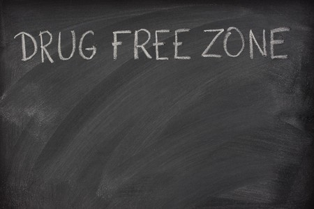 smudge: drug free zone text handritten with white chalk on a school blackboard with strong eraser smudge patterns
