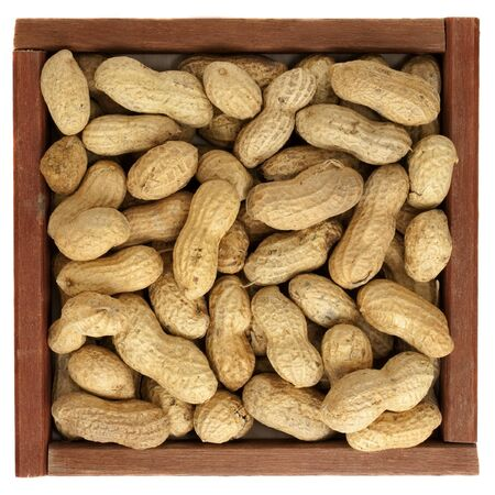 peanuts with shells in  a rustic, square, wooden box or frame, isolated on white photo