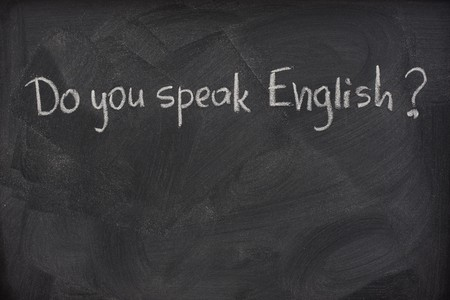 do you speak English question handwritten with white chalk on a blackboard with eraser smudges Stock Photo