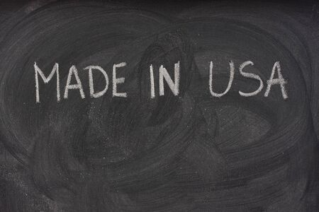 made in USA phrase handwritten with white chalk  on a blackboard with eraser smudges and copy space below photo