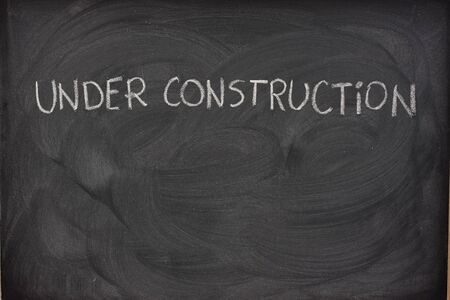 under construction phrase handwritten with white chalk  on a blackboard with eraser smudges and copy space below photo