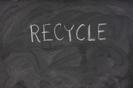 recycle handwritten with white chalk on a school blackboard with eraser smudges photo