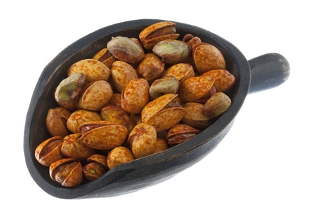 chili lemon roasted pistachio nuts on a rustic, wooden scoop, isolated on white Stock Photo - 4367616