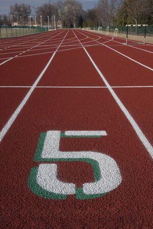 witte baan nummer vijf op een startlijn rode atletiekbaan Stockfoto