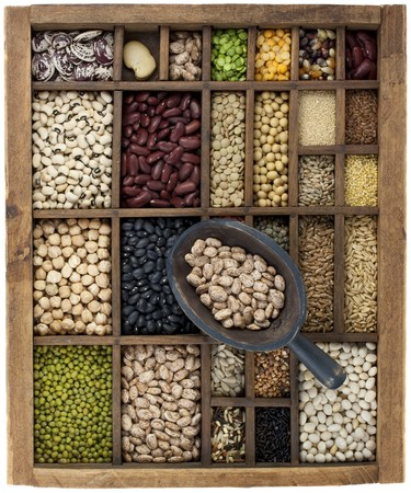 typesetter: vintage, wooden typesetter case with variety of beans, lentils, peas, grains and seeds with a scoop of pinto