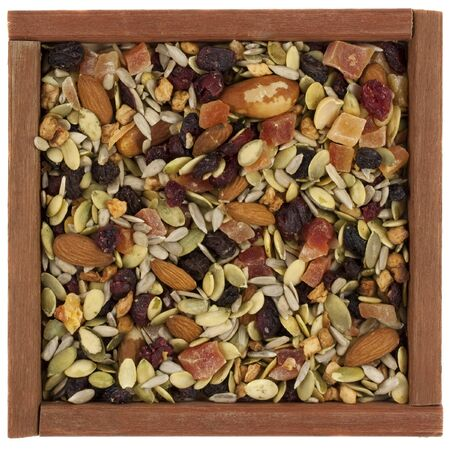 trail mix with pumpkin, sunflowers seeds, almonds, dried papaya,  cranberries, raisins, apples, Brazilian nuts in a rustic wooden box or frame  isolated on white Stock Photo - 4434650
