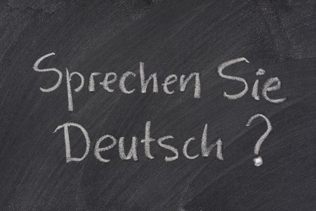deutsch: Sprechen Sie Deutsch? Do you speak German question handwritten with white chalk on a blackboard with eraser smudges Stock Photo