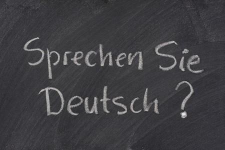 Sprechen Sie Deutsch? Do you speak German question handwritten with white chalk on a blackboard with eraser smudges Stock Photo