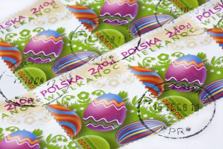 Easter (Wielkanoc) - colorful eggs and floral folk decorations on Polish post stamps canceled in Warsaw with original envelope as background
