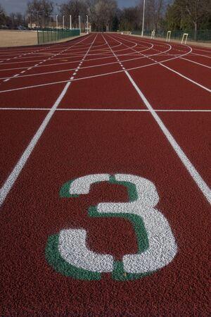witte rijstrook nummer drie op een startlijn rode atletiekbaan Stockfoto