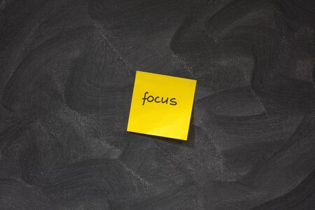chaotic: yellow sticky note with word focus posted on blackboard with chaotic white chalk eraser patterns Stock Photo