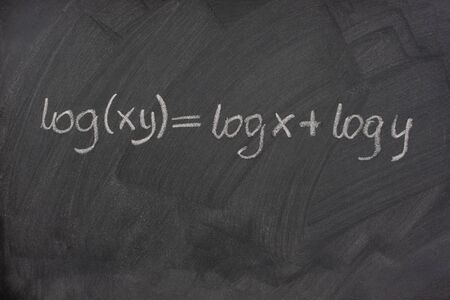 multiplication: logarithm formula (reduction of multiplication to addition) handwritten with white chalk on a school blackboard with eraser smudges and pattern Stock Photo