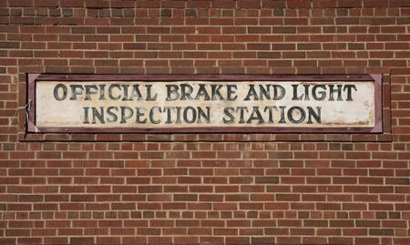 vintage brake and light inspection sign against red brick wall from an old garage Stock Photo