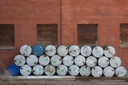 abandoned factory: stack of empty oil drums against brick wall with boarded windows of abandoned factory