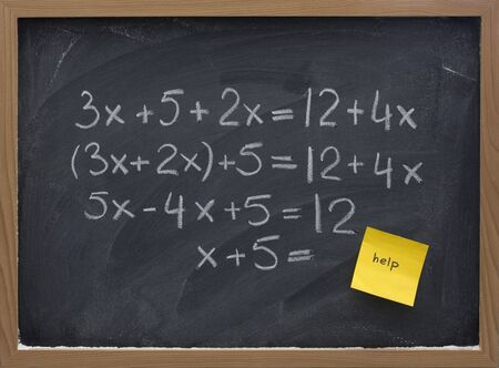 simplification: simple mathematics (equation simplification) on blackboard with a yellow sticky note calling for help Stock Photo
