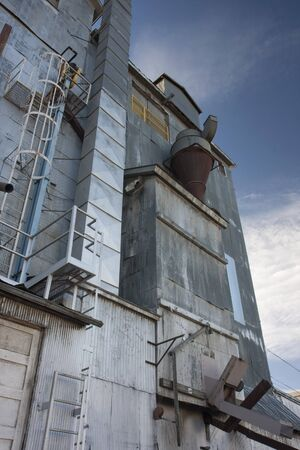industrial background - a metal exter of old grain elevator with pipes, ducts, ladders and chutes against sky Stock Photo - 4491442