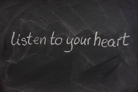 smudge: listen to your heart phrase handwritten with white chalk on a blackboard with eraser smudge patterns