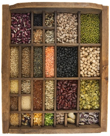 typesetter: vintage, wooden typesetter case (drawer) with variety of beans, lentils, peas, grains and seeds isolated on white, white angle view
