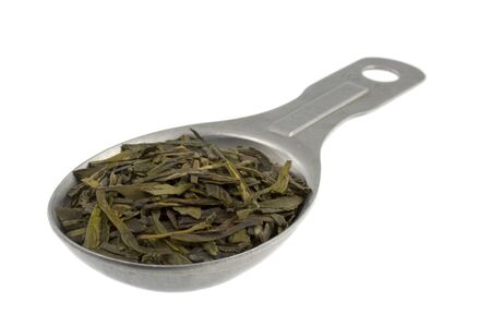 full leaf loose green tea on an old aluminum measuring tablespoon, isolated on white Stock Photo - 4533035