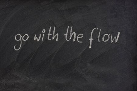 smudge: go with the flow phrase handwritten with white chalk on blackboard with erase smudge patterns