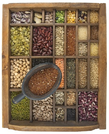 rustic scoop of red quinoa and a variety of beans, lentils, grain, seeds in old wooden typesetter case