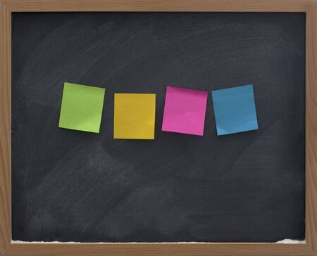 smudge: four blank, colorful (green, yellow, red, blue) sticky notes on blackboard with strong eraser smudge patterns