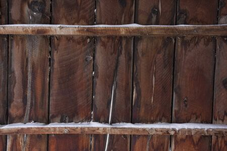 weathered wood of old barn wall with gaps between planks and snow Stock Photo - 4563755