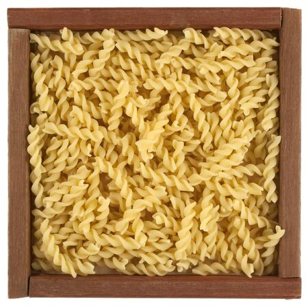 uncooked fusilli pasta in a rustic wooden box or frame isolated on white Stock Photo - 4563757