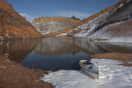 horsetooth reservoir: canoe and Colorado mountain lake (Horestooth Reservoir near Fort Collins)  in early spring with red sandstone cliffs and snow Stock Photo