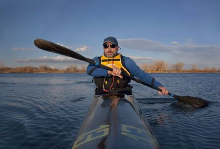 mature paddler exercising in a narrow carbon fiber racing kayak on a lake in early spring in Colorado, thirteen - temporary race number placed on deck by myself