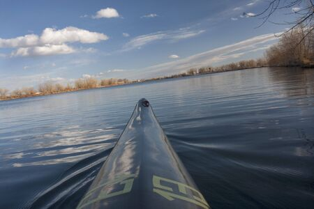 bow of narrow racing kayak turning on calm lake (leaned horizon), early spring in Colorado, thirteen - temporary race number placed on deck by myself Stock Photo - 4593594