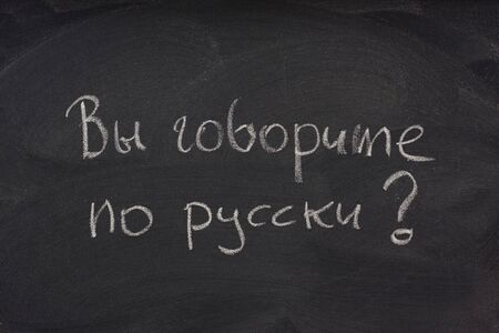 smudges: Govorite po russki? Do you speak Russian question handwritten in cyrilic alphabet with white chalk on a blackboard with eraser smudges Stock Photo