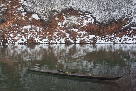 horsetooth rock: long, narrow, carbon fiber, racing sea kayak on mountain lake with high red sandstone cliffs covered by snow, Horsetooth Reservoir near Fort Collins, Colorado, thirteen - temporary race number placed on deck by myself