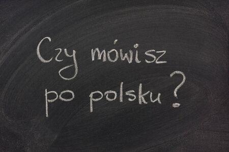 Do you speak Polish question (informal)  handwritten  with white chalk on a blackboard with eraser smudges