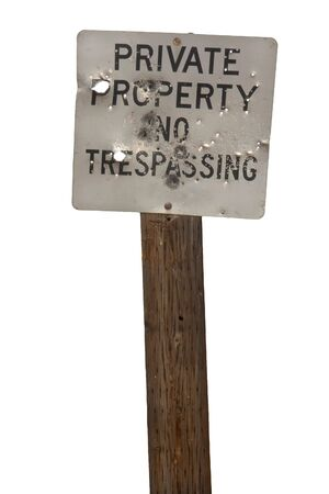 no trespasing, private property sign  with holes from shotgun and bullets photo