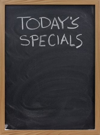 todays specials title handwritten with white chalk on blackboard, copy space below