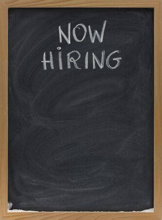 now hiring advertisement handwritten with white chalk on blackboard, copy space below, eraser smudges Stock Photo - 4693413