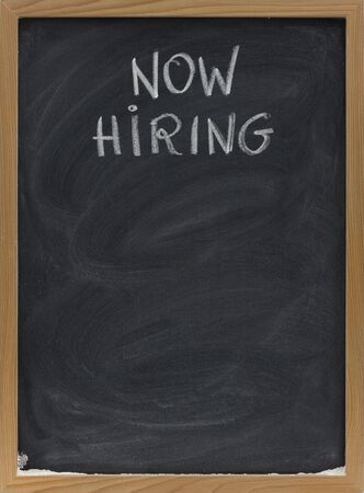 smudges: now hiring advertisement handwritten with white chalk on blackboard, copy space below, eraser smudges Stock Photo