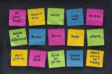 uplifting: notas adhesivas de colores con palabras edificantes y de la sabidur�a motiovational publicado en pizarra manchas con goma de borrar Foto de archivo