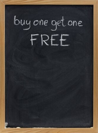 buy one get one free offer - discount sale advertisement handwritten with white chalk on blackboard, copy space below Stock Photo - 4693417