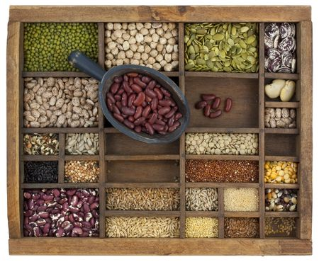 rustic scoop of red kidney beans and a variety of lentils, grain, seeds in old wooden typesetter case